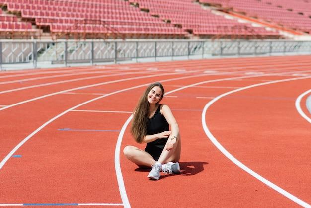Un'allenatrice dai capelli scuri si trova sulla pista rossa dello stadio, vestita in divisa sportiva.