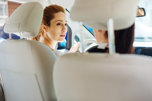 Colleghe. donne di affari astute felici positive che sorridono e che si guardano mentre guidano un'auto