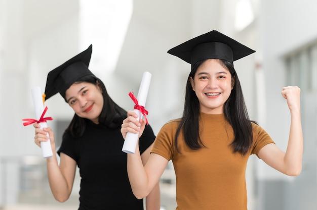 Laureate femminili che indossano cappelli neri, nappe gialle, sorridenti e felici il giorno della laurea