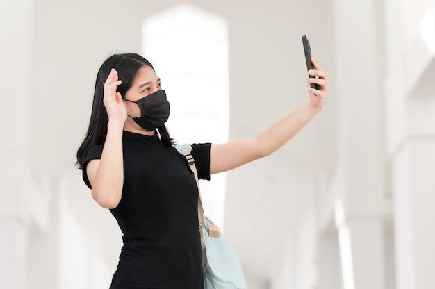 Una studentessa universitaria con un telefono che prende un selfie all'università, torna a scuola,