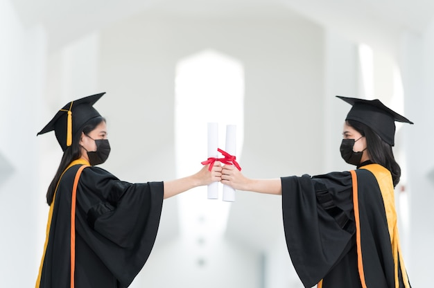 Studentesse universitarie, laureate, indossano cappelli neri, nappe gialle e indossano maschere durante l'epidemia.