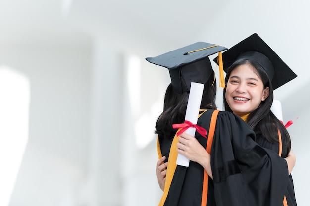 Studentesse universitarie, laureate, cappelli neri, nappe gialle, amiche che abbracciano felicemente.