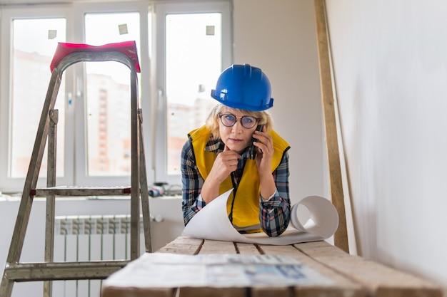 Una lavoratrice edile con un progetto in un giubbotto giallo ispeziona una stanza in un nuovo edificio. una donna di mezza età sta parlando al telefono in un appartamento.