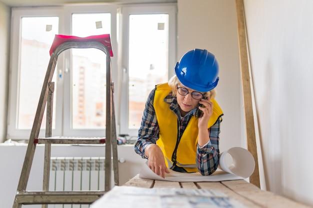 Una lavoratrice edile con un progetto in un giubbotto giallo ispeziona una stanza in un nuovo edificio. una donna di mezza età sta parlando al telefono