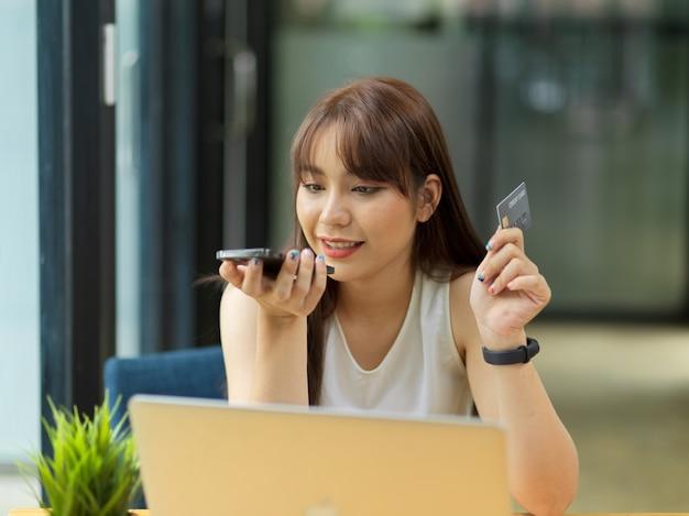 Contatto femminile con il servizio di call center della carta di credito che effettua telefonate tenendo la carta di credito
