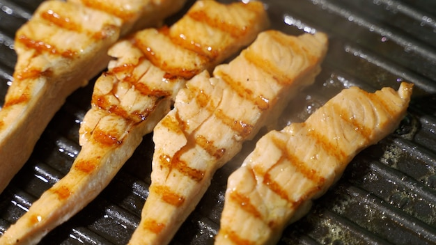 Cuoca condimento bistecche di salmone al pepe nero sulla griglia