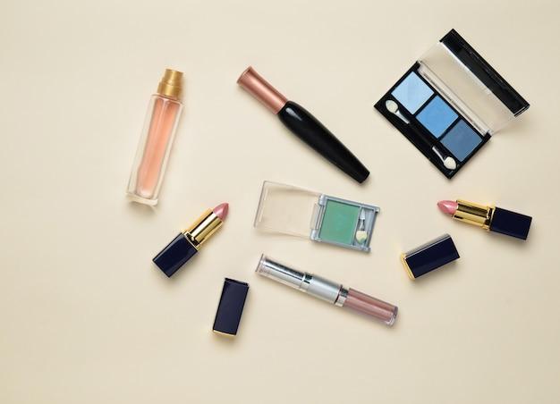 Cosmetici femminili per il layout del trucco. ombre cosmetiche, pennello per il trucco, rossetto per ombretti, bottiglia di profumo. vista piana, vista dall'alto. copia spazio.