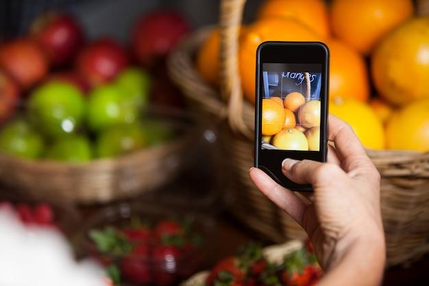 Costumista femminile che cattura maschera delle arance sul telefono cellulare nella sezione organica