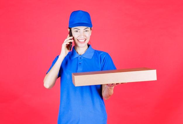 Corriere femminile in uniforme blu che tiene in mano una scatola di cartone per pizza da asporto e parla al telefono.