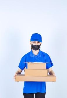 Corriere femminile in maschera e uniforme blu che tiene uno stock di scatole di cartone.