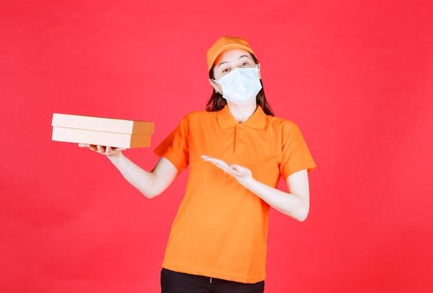 Corriere femminile in codice di abbigliamento e maschera di colore arancione che tiene una scatola di cartone e la mostra.