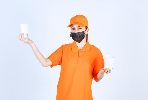 Corriere femminile in uniforme arancione e maschera nera con bevande da asporto in bicchieri di plastica con entrambe le mani