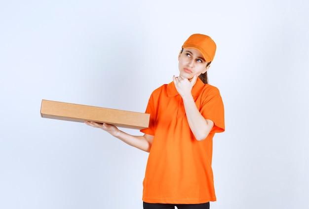 Corriere femminile in uniforme arancione che tiene in mano una scatola di pizza da asporto e sembra premuroso o ha un'idea
