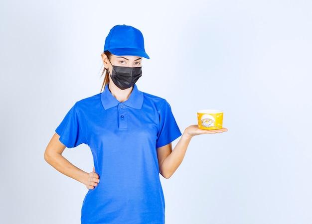 Corriere femminile del ristorante in uniforme blu e maschera facciale con in mano un cibo da asporto.