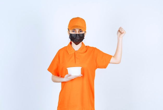 Corriere femminile in uniforme gialla e maschera nera che tiene un bicchiere di plastica e mostra il suo pugno.