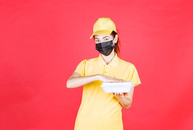 Corriere femminile in uniforme gialla e maschera nera con in mano un pacco da asporto
