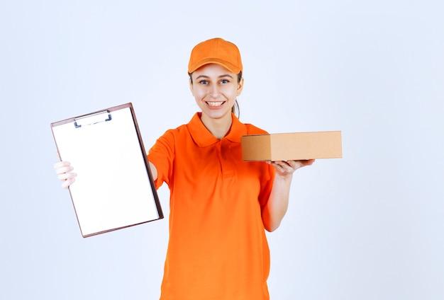 Corriere femminile in uniforme gialla che consegna una scatola di cartone e presenta la lista di controllo al cliente.