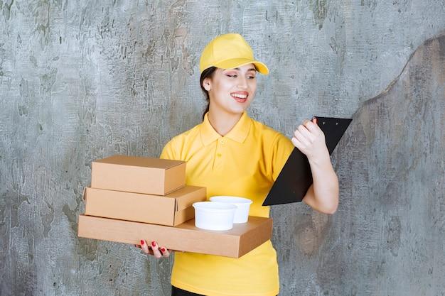 Corriere femminile in uniforme gialla che consegna più scatole di cartone e tazze da asporto e controlla l'indirizzo sulla lista.