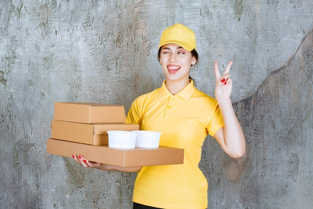 Corriere femminile in uniforme gialla che consegna più scatole di cartone e tazze da asporto e mostra un segno positivo della mano