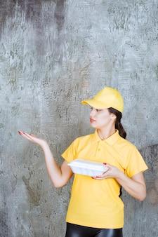 Corriere femminile in uniforme gialla che consegna una scatola bianca da asporto e indica il cliente.