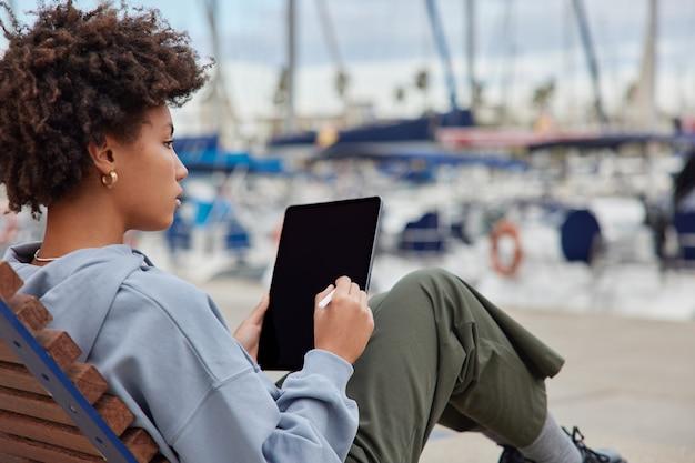 La designer creativa femminile lavora su tablet digitale pensa di creare un nuovo progetto vestito con abiti casual disegna su uno schermo vuoto con lo stilo posa al molo vicino al porto utilizza l'applicazione illustratore