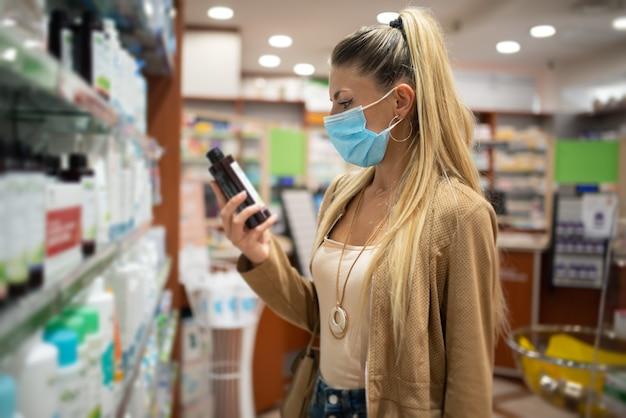 Cliente femminile che controlla un farmaco o un prodotto in una farmacia