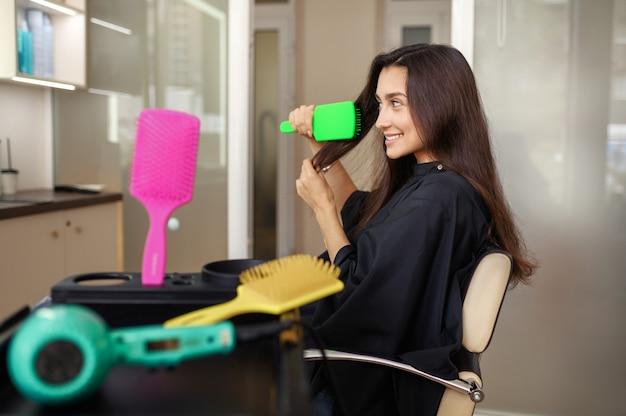 Cliente femminile pettina i capelli nel salone di parrucchiere. donna che si siede sulla sedia nel salone di parrucchiere. affari di bellezza e moda, servizio professionale