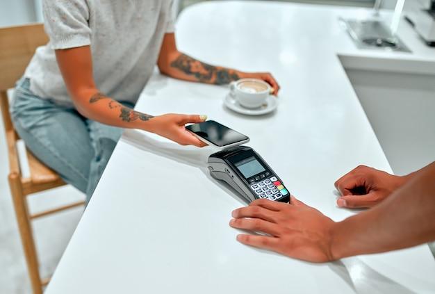Cliente femminile che effettua il pagamento tramite telefono cellulare al banco nella caffetteria con il giovane.