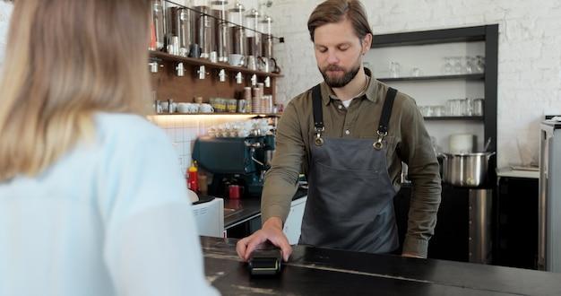 La cliente donna paga il caffè da asporto con la tecnologia di pagamento nfc contactless su smartphone