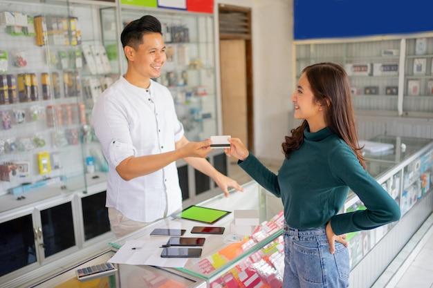 Una cliente donna paga con carta di credito e regala a un uomo