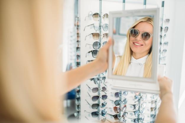 Cliente femminile spara occhiali da sole nel negozio di ottica