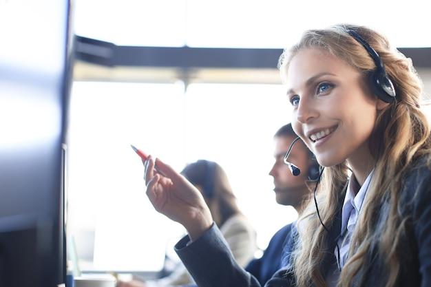 Operatore di assistenza clienti femminile con auricolare e sorridente, con colleghi in background.