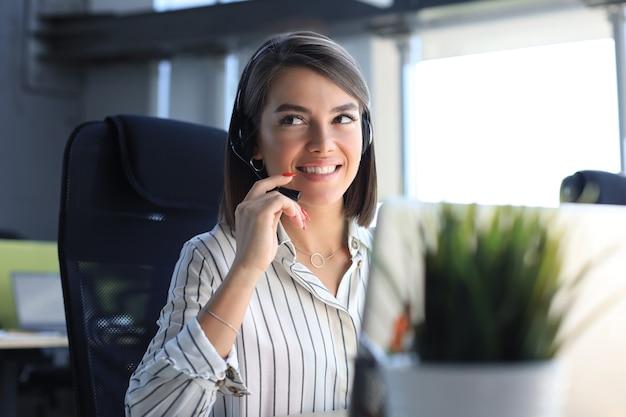 Operatore di assistenza clienti femminile con auricolare e sorridente.