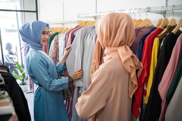 Una cliente donna con il velo sceglie i vestiti quando un cameriere la serve quando sceglie i vestiti su una gruccia