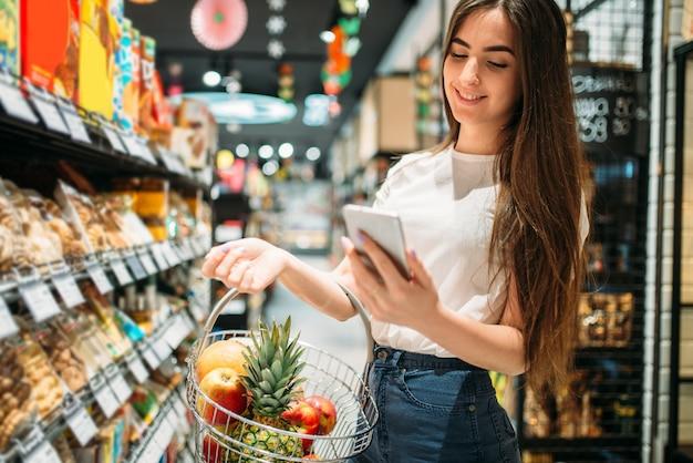 Cliente femminile con cesto di frutta utilizza il telefono cellulare in un supermercato. la donna nel negozio di alimentari