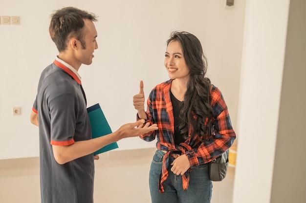 Le clienti femminili sorridono con il pollice in alto agli sviluppatori maschi mentre esplorano all'interno di questa bella nuova casa