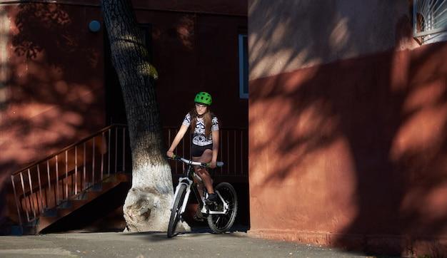 Ciclista femminile che guida la bici tra edifici di strada rossa in giornata di sole estivo.