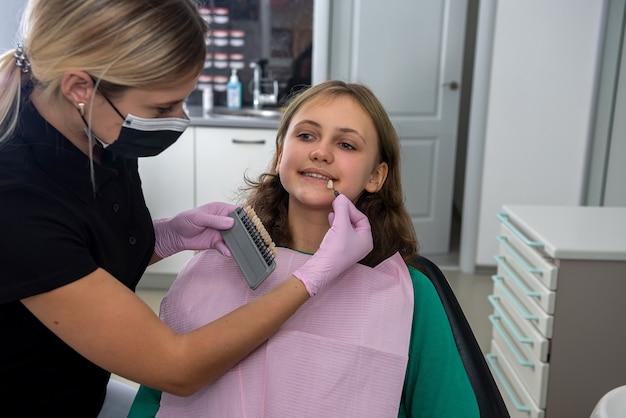 Dentista femminile che controlla e sceglie il colore dei denti con la tavolozza per la ragazza