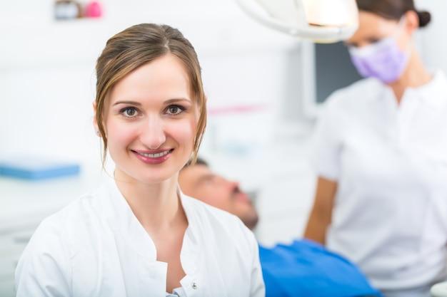 Dentista femminile nel suo intervento chirurgico guardando lo spettatore, il suo assistente sta dando un trattamento a un paziente maschio