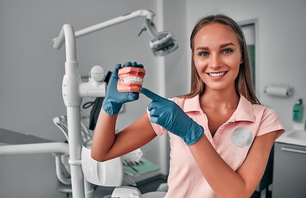 Dentista femminile, che tiene un campione di denti della mascella in uno studio dentistico, formazione nella corretta pulizia dei denti, dimostrazione di igiene orale