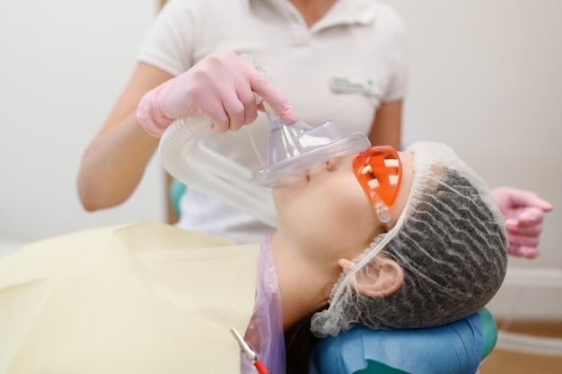 Il dentista femminile mette la maschera sul viso del paziente in clinica, stomatologia