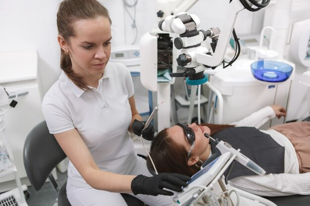Dentista femminile che lavora con il paziente femminile, facendo uso del microscopio dentale