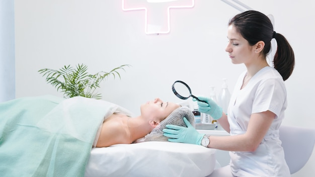 Il dermatologo femminile che esamina il fronte del giovane paziente con la lente d'ingrandimento in clinica o salone di bellezza. concetto di detergente per il viso, pelle e assistenza sanitaria