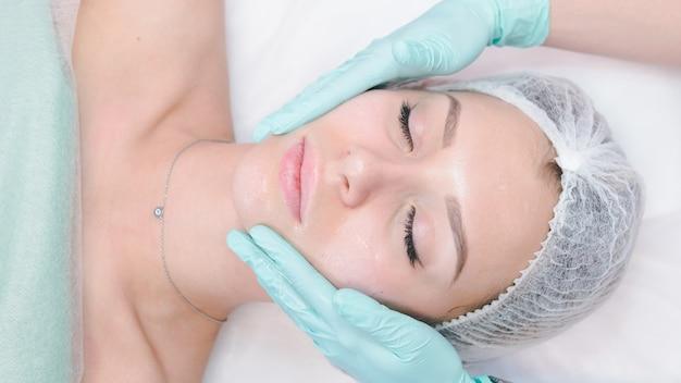 Il dermatologo femminile faccia massaggiato al gabinetto di cosmetologia della bella ragazza o alla clinica di bellezza. concetto di detergente per il viso, pelle e assistenza sanitaria