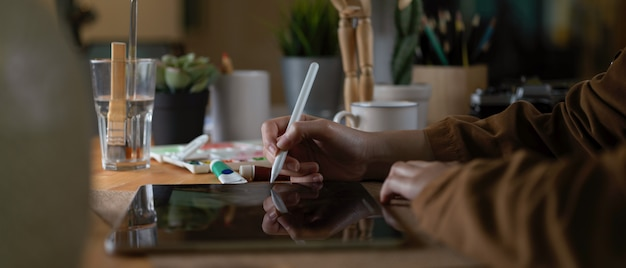 Progettista femminile che lavora alla compressa digitale mentre sedendosi nell'area di lavoro con gli strumenti e i rifornimenti della pittura