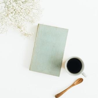 Scrivania femminile con caffè, libro, fiori su superficie bianca