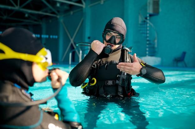 Sub femmina e divemaster maschio in attrezzatura subacquea, lezione nella scuola di immersioni. insegnare alle persone a nuotare sott'acqua, interno della piscina coperta sullo sfondo