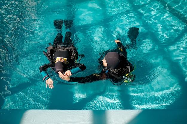 Sub femmina e istruttore maschio in attrezzatura subacquea, lezione nella scuola di immersioni. insegnare alle persone a nuotare sott'acqua, interno della piscina coperta sullo sfondo