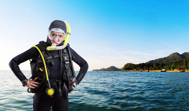 Sportivo subacqueo femminile in muta e attrezzatura subacquea