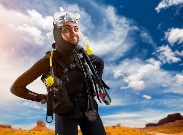 Operatore subacqueo femminile in muta e attrezzatura subacquea pone sulla spiaggia. frogman in maschera e scuba sulla spiaggia, sport subacqueo